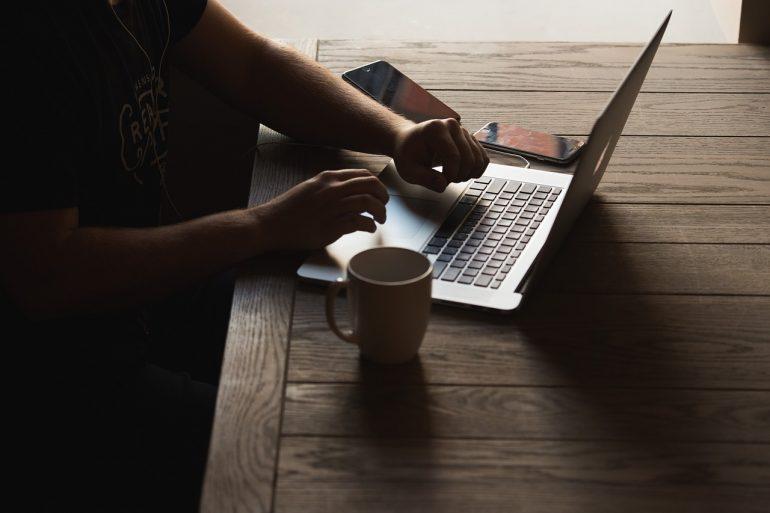 hombre redactando una nota de prensa en una laptop
